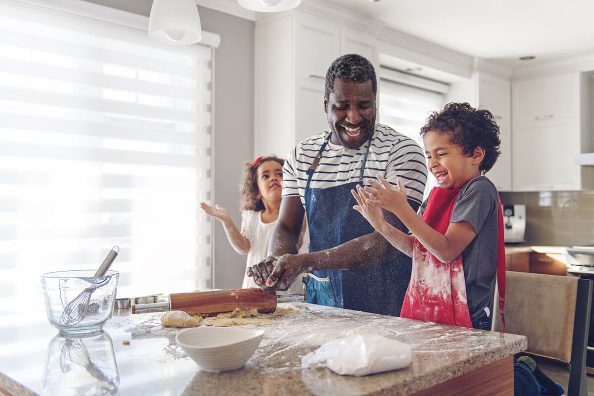 Dad with son and daughter baking at kitchen island