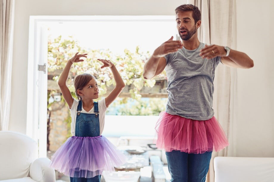 Girl in overalls and purple tutu dances with dad in gray shirt and pink tutu